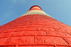 Light House towers into blue sky. A red and white light house towers into the light blue sky Royalty Free Stock Photo