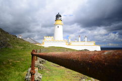 Lighthouse on cliff edge behind old rusty fence bars Royalty Free Stock Photography