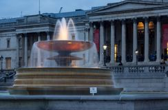 Light illuminates the water in one of the fountains at Trafalgar Square, Westminster, London, UK at dusk. Royalty Free Stock Photos