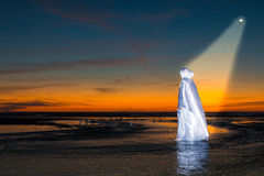 Light of Jesus Christ. Jesus Christ walking in a flowing stream at a beach after sunset Stock Photo