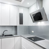 Light kitchen with exhaust hood and hob Stock Image