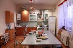 Light kitchen: table, gas stove, fridge Stock Photo