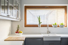 Light kitchen with white countertop. Sink, window and grey furniture stock photo
