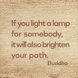 Light a lamp Buddha wood. If you light a lamp for somebody, it will also brighten your path - famous quote of Gautama Buddha printed on grunge wooden board royalty free stock photo