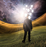Light Landscape. Man in environment filled with light has bulbs representing concepts hovering over his head Royalty Free Stock Photography