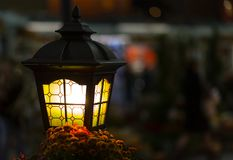 Light lantern street in the dark. Lamp with stained glass windows close-up on a blurred city background Royalty Free Stock Image