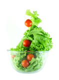 Light lettuce and tomatoes flying salad concept. Light lettuce and cherry tomatoes salad in transparent bowl isolated on white lightness concept Royalty Free Stock Photography