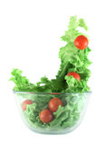 Light lettuce and tomatoes flying salad concept. Light lettuce and cherry tomatoes salad in transparent bowl isolated on white lightness concept Stock Photos