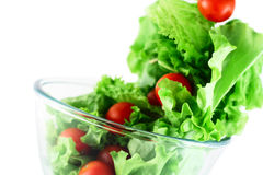 Light lettuce and tomatoes flying salad concept. Light lettuce and cherry tomatoes salad close-up isolated on white lightness concept Royalty Free Stock Images