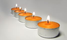 Light line. Orange candles on the grey background royalty free stock photography