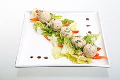 Light lunch wiht rice patties and salad. Rice patties and salad in a square dish on white Royalty Free Stock Photos