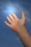 Light Magic. Hand of a man reaching to towards a blue sky with a light glow coming from his forefinger Stock Images