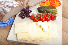 Light meal on rustic wooden board with german bread, cheese, mozzarella, fruits and vegetables Stock Photos
