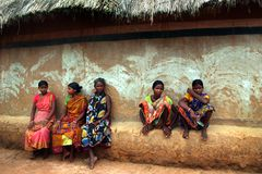 Light mode. Sitting on a bench made of mud attached to their house a group of Tribal woman gossiping in front of a painted wall at Amaridanga, India Royalty Free Stock Image