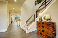 Light modern hallway design boasts steamer trunk dresser. Light modern hallway design boasts vintage steamer trunk dresser next to staircase with metal Stock Images