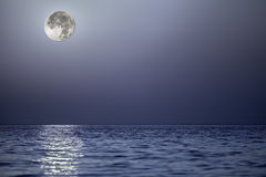 Light from the moon reflecting off a calm blue sea Stock Images
