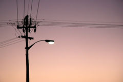The light at night. A single old streetlamp against a sunset sky stock image