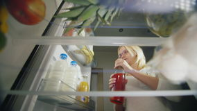 Light night snack, unhealthy food. A young woman in glasses opens a refrigerator, drinks juice and takes an apple. View. From inside the refrigerator. pov video stock video
