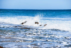 Light ocean plunging and collapsing waves, breaking on the rocks natural blue ocean colour, foamy water Stock Photos