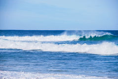 Light ocean plunging and collapsing waves, natural blue ocean colour, foamy water Royalty Free Stock Images