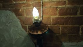 Light on old brick wall. Lamp lamp sconce on the old brick wall in the restaurant stock video