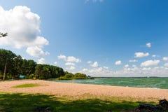 Light orange beach and green water under blue sky Stock Photo