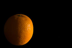 Light on orange in darkness. Light shining on orange fruit with half in darkness Stock Images