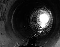 Light on the other side. Big pipeline with sunlight on the opposite side. Water on the bottom of the pipe. Black & white image Stock Photography