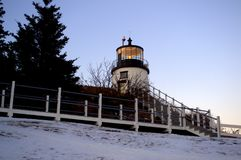 The light is on!  Owls Point Head Lighthouse. The light is on!  Owls Head Lighthouse, Rockland Maine, USA.  Wintertime, snow Stock Images