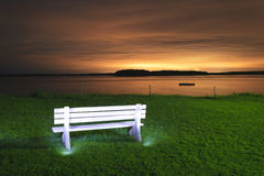 Light painted bench at sunset. Light painted white bench iwith a dock floating in a bay at night, Maine, USA stock photo