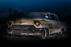 Light painted at night and in very beat up and in poor condition Classic American car from the fifties. Beige and rusty classic American car from the fifties stock photos