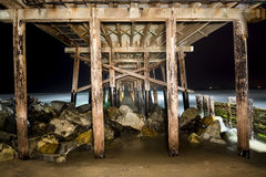 Light painted pier. A light painted image of Balboa Pier underside taken at 4:00 AM with a slow exposure shows the intricate detail of the structure.  The ocean Royalty Free Stock Photography