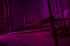 Light painted in pink abandoned bed in dark room. Halloween part Stock Photo