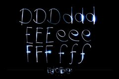 Light Painting Alphabet - Light Serge Font DEF. On black background Royalty Free Stock Photos