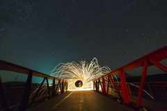 Light painting art concept. Long exposure shot of spinning steel. Wool in abstract circle making firework showers of bright yellow glowing sparkles on long stock photos