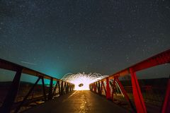 Light painting art concept. Long exposure shot of spinning steel wool in abstract circle making firework showers of bright yellow. Glowing sparkles on long royalty free stock photo