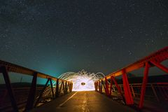 Light painting art concept. Long exposure shot of spinning steel wool in abstract circle making firework showers of bright yellow. Glowing sparkles on long royalty free stock photography