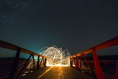 Light painting art concept. Long exposure shot of spinning steel wool in abstract circle making firework showers of bright yellow stock image