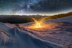 Light painting art. Spinning steel wool in abstract circle, firework of bright yellow glowing sparkles on snowy white valley on. Woody mountain ridge and blue royalty free stock photography