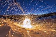Light painting art. Spinning steel wool in abstract circle, firework showers of bright yellow glowing sparkles on winter snowy. Valley on mountain ridge and royalty free stock photography
