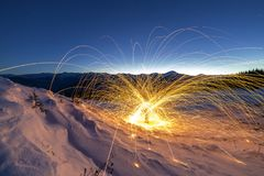 Light painting art. Spinning steel wool in abstract circle, firework showers of bright yellow glowing sparkles on winter snowy. Valley on mountain ridge and stock photos