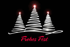 Light painting Christmas trees with lettering. Merry Christmas in German Stock Photo
