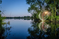 Light-painting effect by side of lake Stock Image