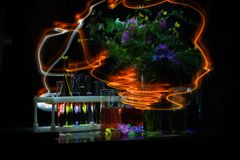 Light painting with a flashlight in the dark at a long exposure. chemical dishes and flowers royalty free stock images