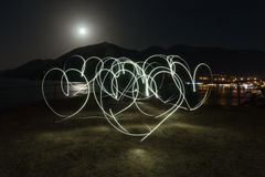 Light painting heart shapes over mountains, sea and night town background. Love. Royalty Free Stock Image