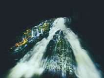 Light painting in night waterfall in autumn stream. Blurred foamy water on mossy rock with colorful leaves. Light painting in night waterfall in autumn stream royalty free stock image