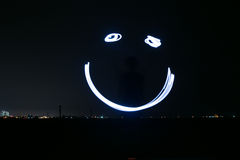 Light Painting Smile Face. Light painting, or light drawing, is a photographic technique in which exposures are made by moving a hand-held light source while Stock Photography