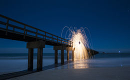 Light Painting with Steel Wool at a pier on the beach Stock Photos