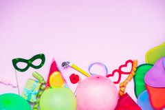 Light pink Festive background with party tools and decoration - baloons, funny carnival masks, festive tinsel. Happy birthday gree. Ting card. Design concept royalty free stock image