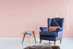 Light pink room with armchair. Light pink room with blue armchair and wood side table Stock Photos